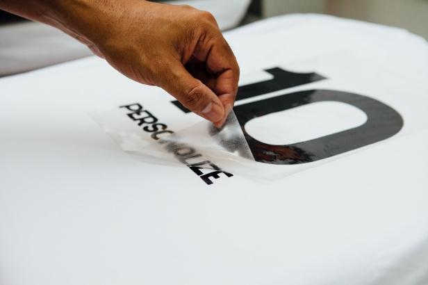 Área de confecção dos produtos: mão retirando adesivo da camiseta personalizada