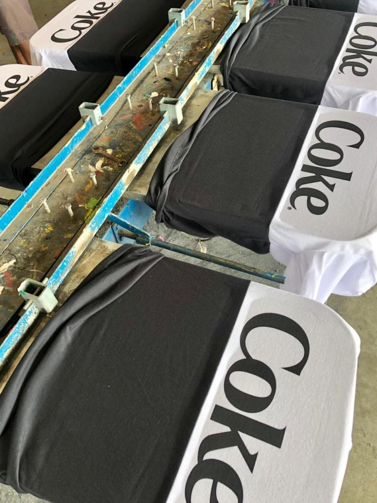 Camisetas brancas e pretas personalizadas em atacado sendo feitas em fábrica de personalização
