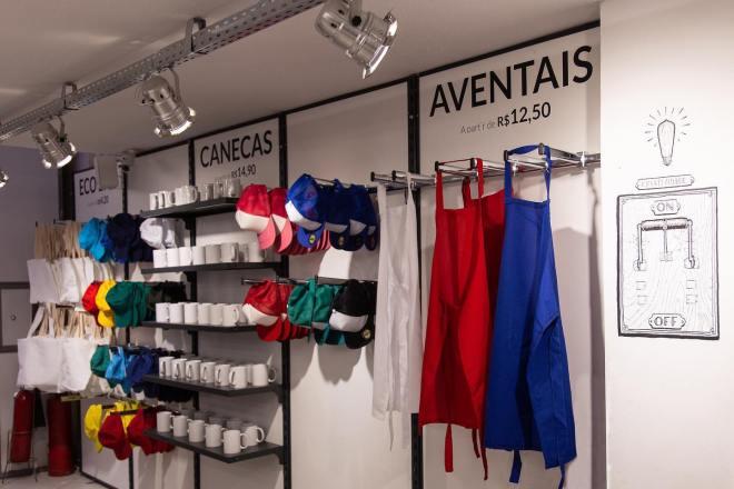 Espaço com a exposição dos produtos personalizaveis, como: aventais, bonés, canecas e ecobags