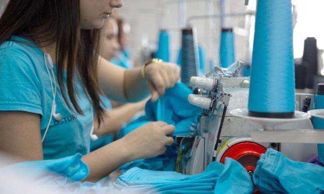 Mulher trabalhando em uma fábrica de camisetas costurando camisetas azuis