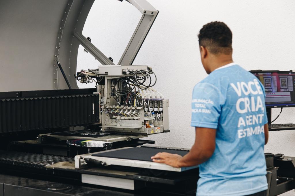 Homem operando máquina de personalização em fábrica de personalizar