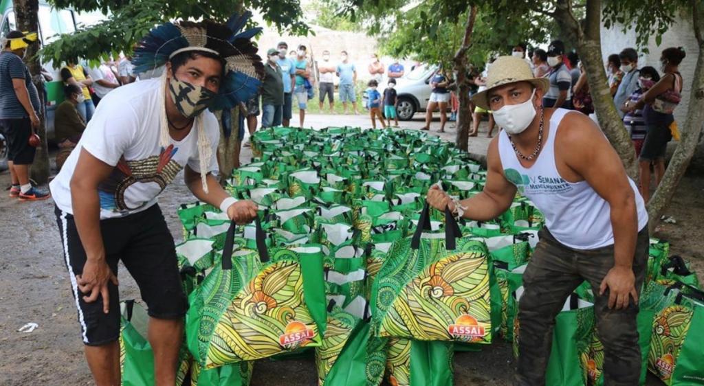 Homens segurando sacolas de alimentos