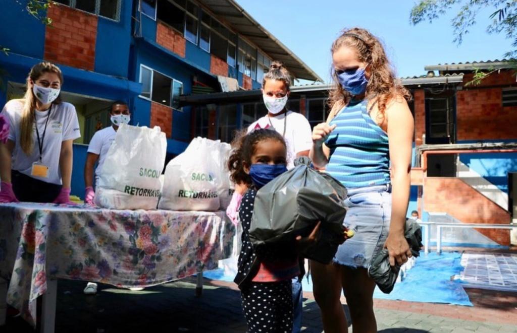 Criança segurando sacola com doação do projeto