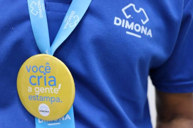 Camiseta Azul com a estampa da Dimona e crachá pendurado com Botton da Dimona