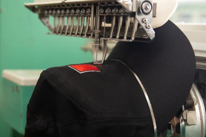 Boné preto sendo personalizado por uma máquina de bordado