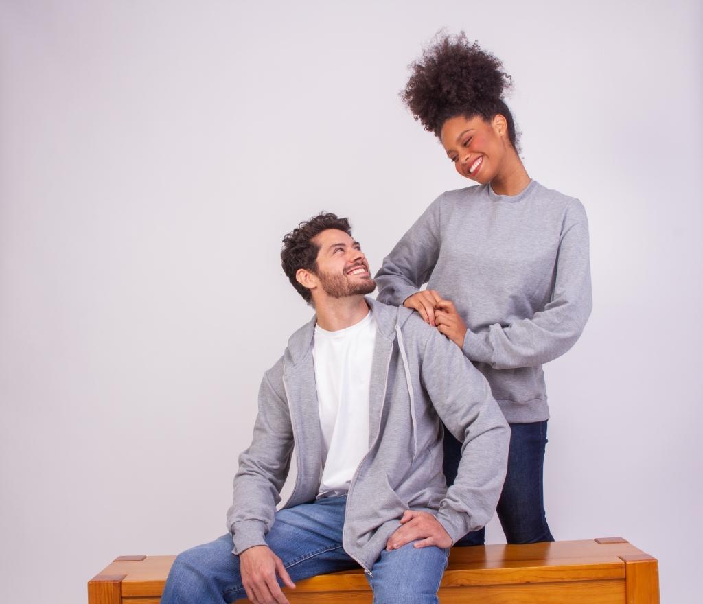 Casal se olhando e vestindo moletons cinzas. O homem está com um moletom com zíper e a mulher com um moletom sem zíper.