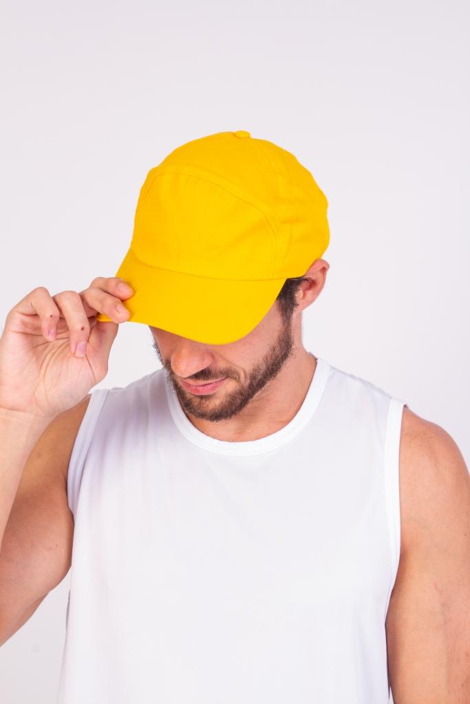 Homem com um boné de brim amarelo na cabeça
